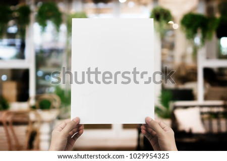 Hand holding blank paper poster design for menu at restaurant, Mock up space for display of menu or design. #1029954325