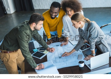 high angle view of multicultural businesspeople with blueprint in office #1029958021