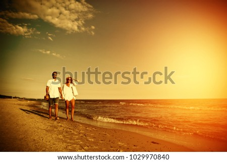 Two lovers on beach and summer golden sunset time.  #1029970840