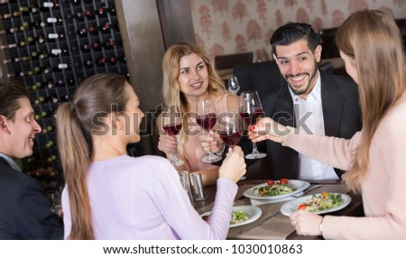Group of friends enjoying evening meal in cozy restaurant  #1030010863