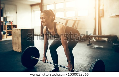 Fit young woman in sportswear smiling while lifting heavy weights during a workout session in a gym #1030032865