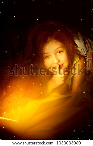 Little caucasian 6-8 years old girl reading a book under bed cover in the bed night under bed cover with portable LED lighting Book Reading. Children, immagination and modern tecnology concept Royalty-Free Stock Photo #1030033060