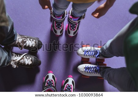 partial view of family in roller skates standing on roller rink