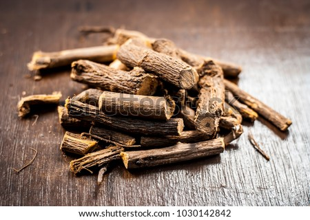 Close up of Ayurvedic herb Liquorice root,Licorice root, Mulethi or Glycyrrhiza glabra root on a wooden surface is very much beneficial for Soothes your stomach,poisoning, stomach ulcers, etc. #1030142842