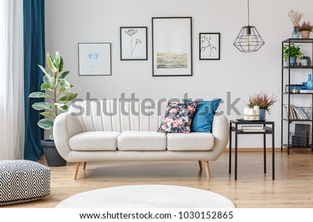 Floral pillow on beige sofa next to table with candles in living room interior with pouf and posters #1030152865