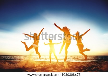 Group of four happy girls runs and jumps against sunset sea beach. Tropical vacations concept #1030308673