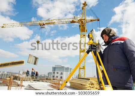 One surveyor worker working with theodolite transit equipment at construction site outdoors #103035659