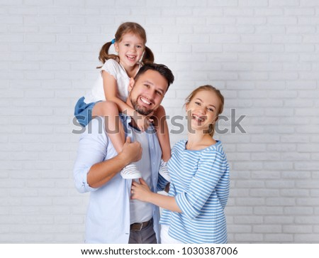 happy family mother father and child daughter near an empty brick wall