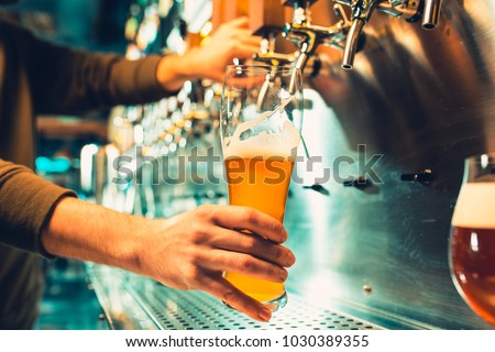 Hand of bartender pouring a large lager beer in tap. Soft, vintage instagram effect on photo. Pouring beer for client. Side view of young bartender pouring beer while standing at the bar counter #1030389355