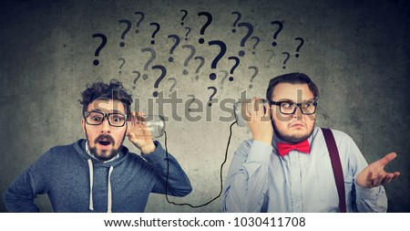 Two funny looking men having troubled communication  Royalty-Free Stock Photo #1030411708