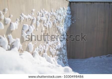 Snow chunks on the wall #1030498486