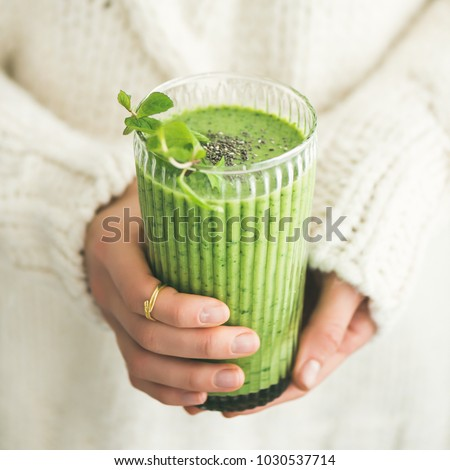 Matcha green vegan smoothie with chia seeds and mint in glass in hands of female wearing white sweater, square crop. Clean eating, detox, alkaline diet, weight loss concept #1030537714