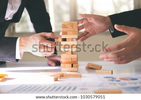 Businessman hand stop dominoes continuous toppled or risk with copyspace. Business risk, strategy and planing concept idea. #1030579051