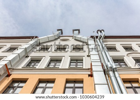 old building facade, bottom view. wall with metal ventilation pipes. #1030604239