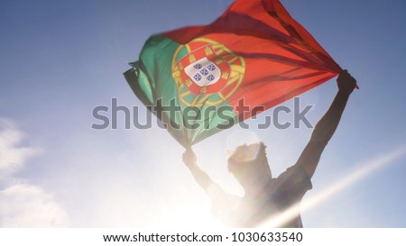 Young man holding portuguese national flag to the sky with two hands at the beach at sunset portugal #1030633540