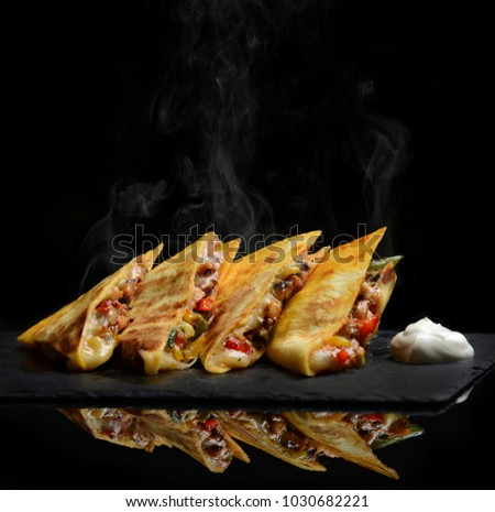 Mexican Quesadilla wrap with chicken   sweet pepper sour cream and salsa hot with steam smoke on black background #1030682221