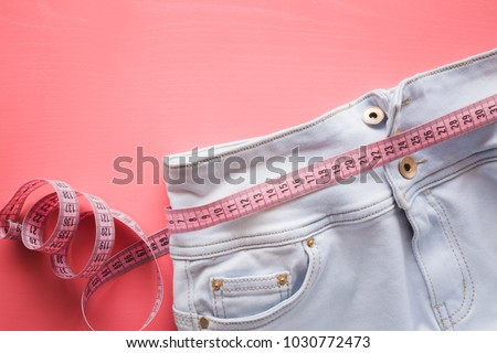 Measure tape with light blue jeans on the pastel pink background. Women diet. Mock up for healthy lifestyle, body slimming, weight loss or dressmaker's offer or other ideas. Empty place for text. Royalty-Free Stock Photo #1030772473