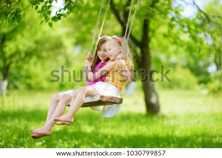 Two cute little sisters having fun on a swing together in beautiful summer garden on warm and sunny day outdoors. Active summer leisure for kids. #1030799857