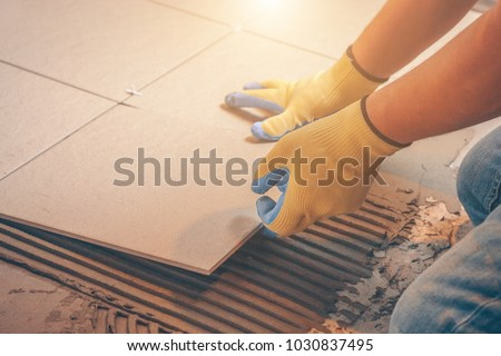 The tile glues the tile to the floor with a glue applied by a notched trowel Royalty-Free Stock Photo #1030837495