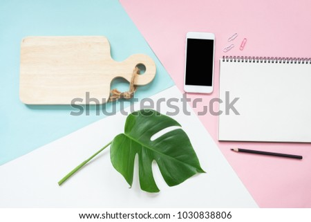 Lifestyle cooking lover concept. Mock up with a smartphone, open notepad and cutting board on pastel background view from above #1030838806