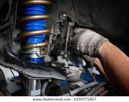 maintaining a car shock absorbers at garage. #1030975867