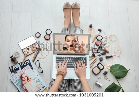 Woman sitting on floor with laptop and watching online training for professional makeup artist #1031005201