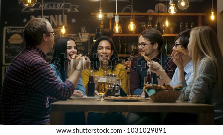 In the Bar/ Restaurant Group of Diverse Young People Eat Slices of Pizza Pie. They Talk, Tell Jokes and Have Fun in This Stylish Establishment. #1031029891