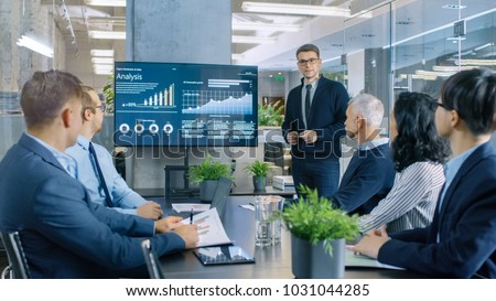 Young Stock Trader Shows to the Executive Managers Cryptocurrency and Trade Market Correlation Pointing at the Wall TV. Royalty-Free Stock Photo #1031044285