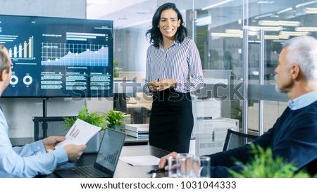 Beautiful Businesswoman Gives Report/ Presentation to Her Business Colleagues in the Conference Room, She Shows Graphics, Pie Charts and Company's Growth on the Wall TV. #1031044333