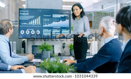 Beautiful Businesswoman Gives Report/ Presentation to Her Business Colleagues in the Conference Room, She Shows Graphics, Pie Charts and Company's Growth on the Wall TV. Royalty-Free Stock Photo #1031044339
