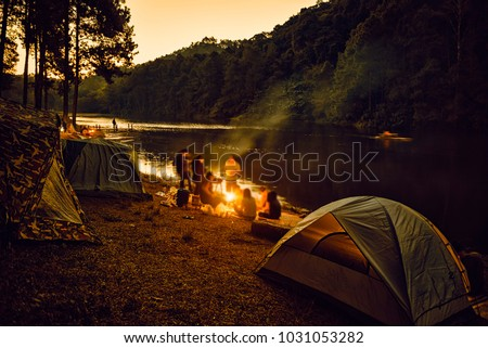 Group of backpackers relaxing near campfire, tourist background. #1031053282