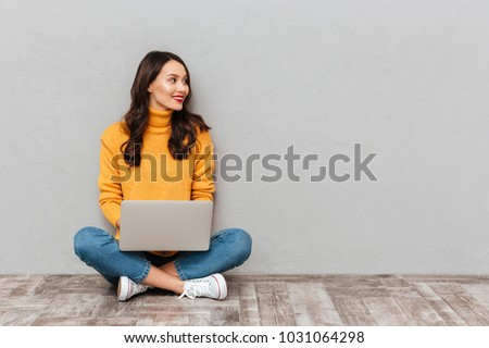 Smiling brunette woman in sweater sitting on the floor with laptop computer and looking away over gray background