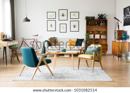 Stylish vintage furniture in a spacious flat interior with beige sofa, chairs and posters on the wall Royalty-Free Stock Photo #1031082514