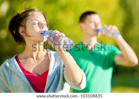 Man and woman drinking water from bottle after fitness sport exercise #103108835