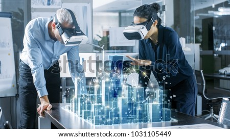 Male and Female Architects Wearing  Augmented Reality Headsets Work with 3D City Model. High Tech Office Professional People Use Virtual Reality Modeling Software Application. #1031105449