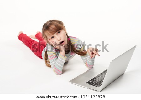 Surprised little girl lying on stomach on the floor with laptop, pointing at screen with amazement, over white background #1031123878