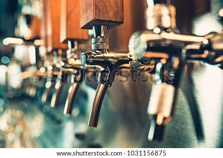 The beer taps in a pub. nobody. Selective focus. Alcohol concept. Vintage style. Beer craft. Bar table. Steel taps. Shiny taps. #1031156875