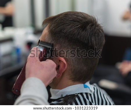 The hands of young barber making haircut to attractive man in barbershop #1031223319