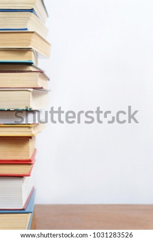 Stack of different books on a table against a white wall background #1031283526
