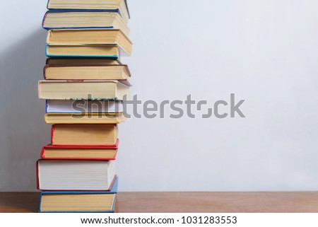 Stack of different books on a table against a white wall background #1031283553
