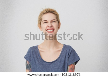Portrait of young blonde  stylish girl with tattoos smiling and feels happy, keeps teeth clenched. Isolated over white wall #1031318971
