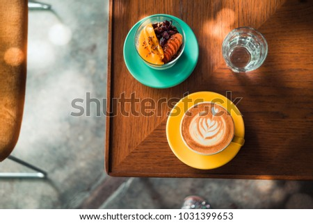 Flat white coffee in yellow cup with chia pudding dessert on turquoise plate from above. Wooden table at the minimalist hipster coffee shop. Vintage filter effect. Copyspace  #1031399653