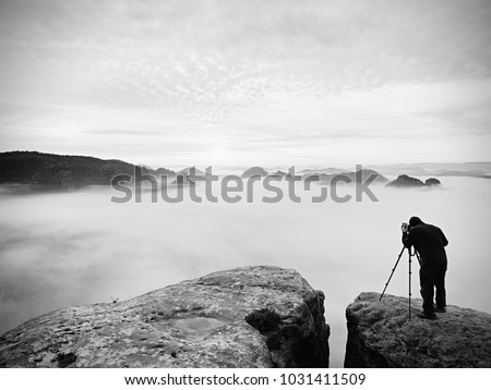 Photographer framing picture with eye on viewfinder. Photo enthusiast  enjoy work of fall nature on rocky summit. Dreamy landscape, misty sunrise in a beautiful valley below
