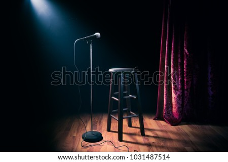 microphone and stool on a stand up comedy stage with reflectors ray, high contrast image Royalty-Free Stock Photo #1031487514
