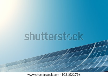 Photovoltaic modules of huge solar panels with clear blue sky and sun on background #1031523796