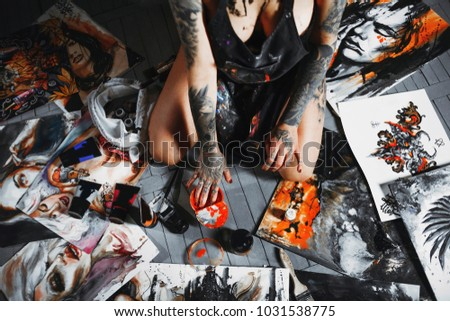 Around the artist's picture.  The artist put her fingers in the paint #1031538775