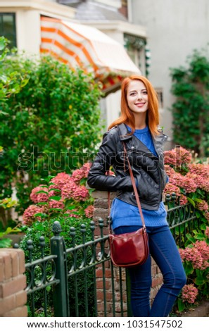Young redhead woman standing at street in the city of Amsterdam in springtime.  #1031547502