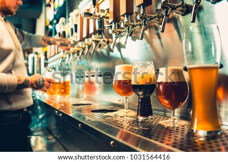 We meet oktoberfest. Hand of bartender pouring a large lager beer in tap. Pouring beer for client. Side view of young bartender pouring beer while standing at the bar counter #1031564416