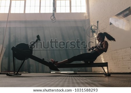 Woman doing cardio workout on rowing machine in the gym. Female exercising in fitness club. Royalty-Free Stock Photo #1031588293