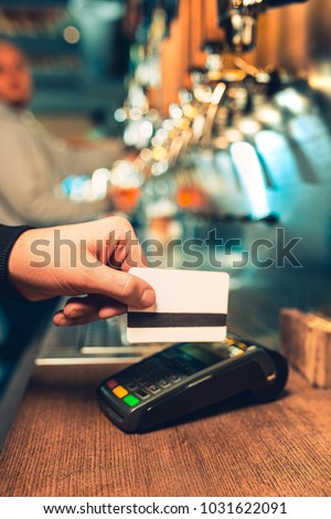 Man using payment terminal. White credit card. Hand use credit card. Bar table. The beer taps in a pub. Costumer concept. Service concept. #1031622091